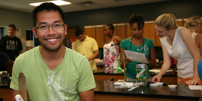 Photo of male student smiling with other students in the background