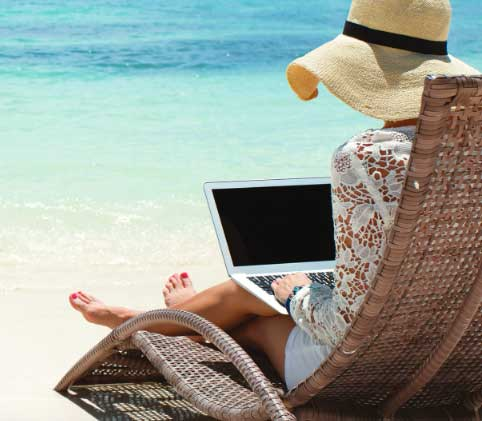 Women on beach with laptop